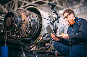 Aircraft engineer in a hangar using a laptop while repairing and maintaining an airplane jet engine