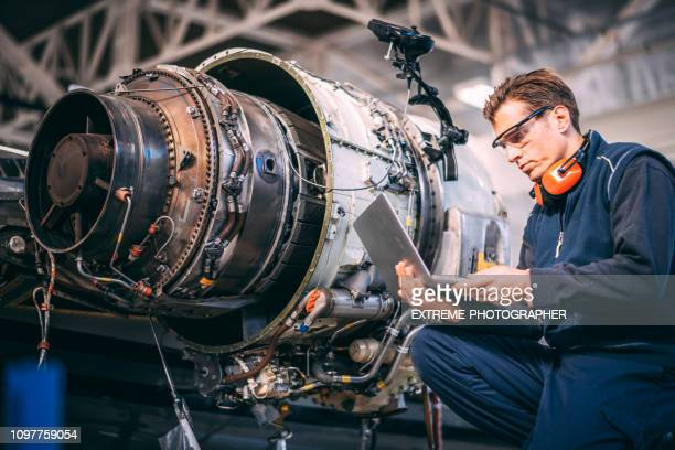 aircraft engineer in a hangar using a laptop while repairing and maintaining an airplane jet engine - engineering stock pictures, royalty-free photos & images