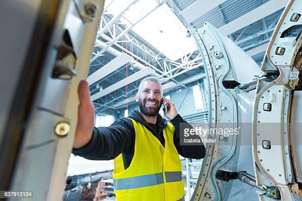 Aircraft engineer talking on smart phone in a hangar