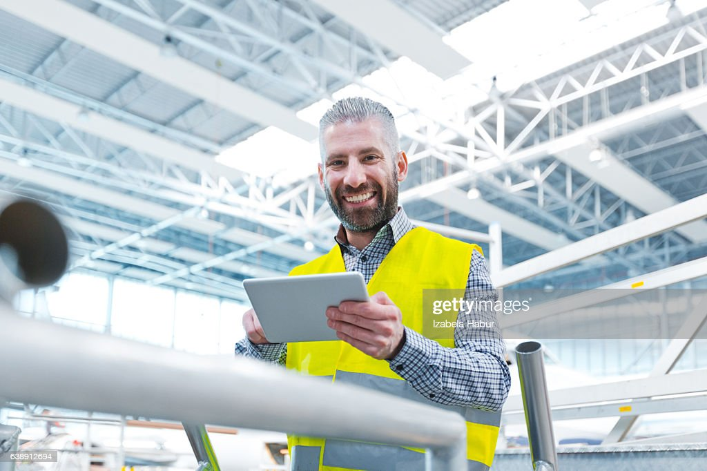 Aircraft engineer using a digital tablet in a hangar : Stock Photo