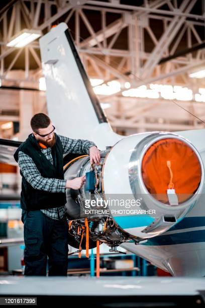 flugzeugingenieur arbeitet an einem defekt an einem düsentriebwerk eines kleinflugzeugs, das in einem servicehangar geparkt ist - flugzeugheck stock-fotos und bilder