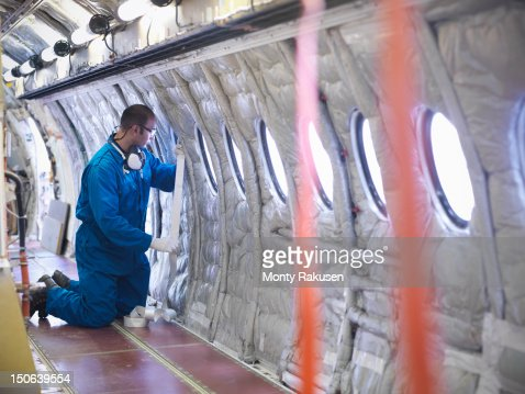 Aircraft engineer working on interior of 737 jet airplane