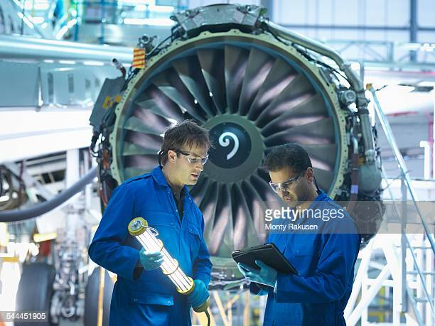 Aircraft engineers discussing maintenance details on digital tablet in front of jet engine in aircraft maintenance factory
