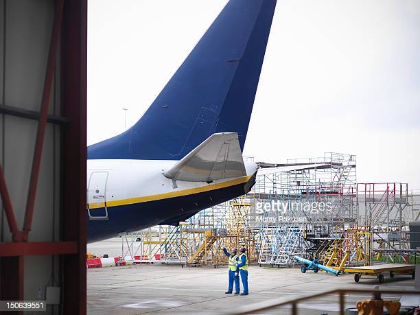 aircraft engineers guiding 737 jet plane into hangar - airplane tail stock pictures, royalty-free photos & images