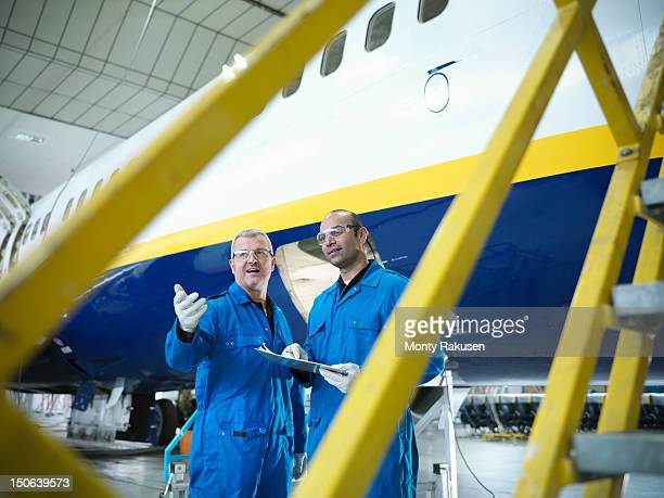 Aircraft engineers in discussion in front of jet aircraft