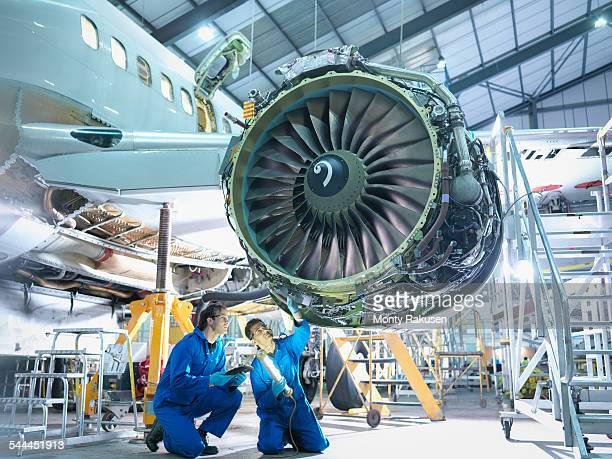 Aircraft engineers inspecting jet engine in aircraft maintenance factory