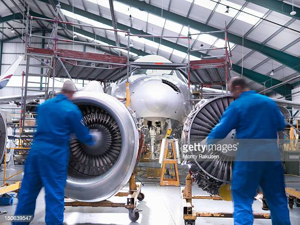 aircraft engineers inspecting jet engines of jet airplane - aerospace stock pictures, royalty-free photos & images