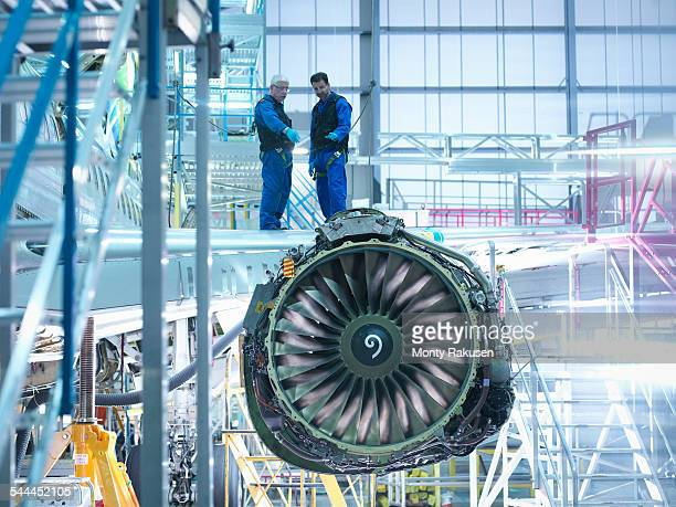 aircraft engineers standing on wing with jet engine in aircraft maintenance factory - jet engine stock photos and pictures
