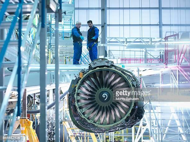 aircraft engineers standing on wing with jet engine in aircraft maintenance factory - halle gebäude stock-fotos und bilder