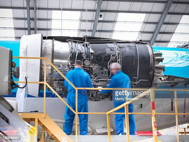 Aircraft engineers working on 737 jet engine in airport