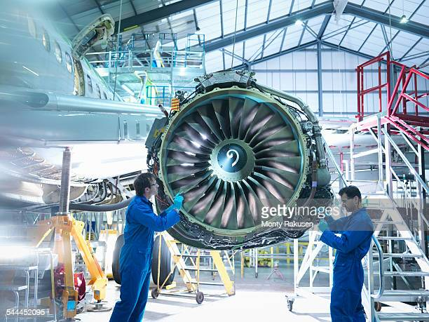 Aircraft engineers working on jet engine in aircraft maintenance factory