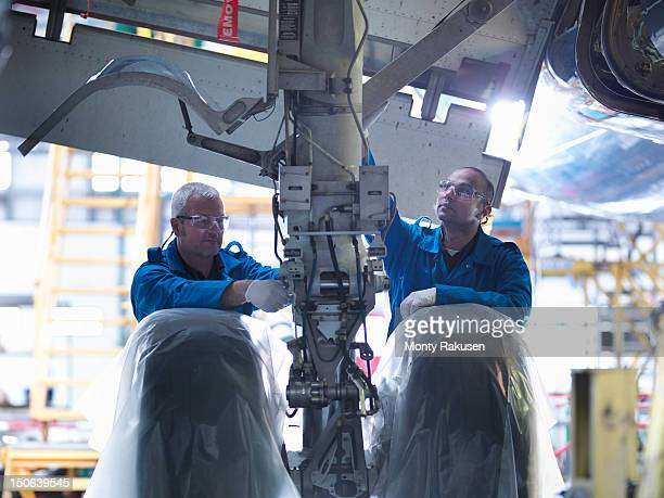 Aircraft engineers working on undercarriage area and landing gear of 737 jet plane