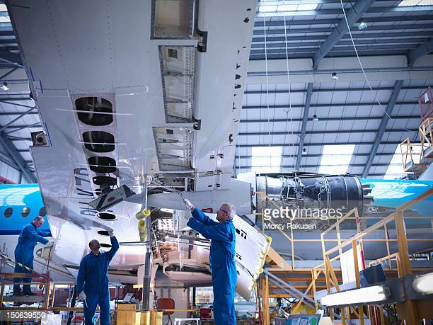 Aircraft engineers working on underside of wing of 737 jet plane