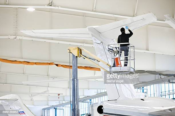 aircraft factory worker painting airplane tail assembly - aircraft assembly plant stock pictures, royalty-free photos & images
