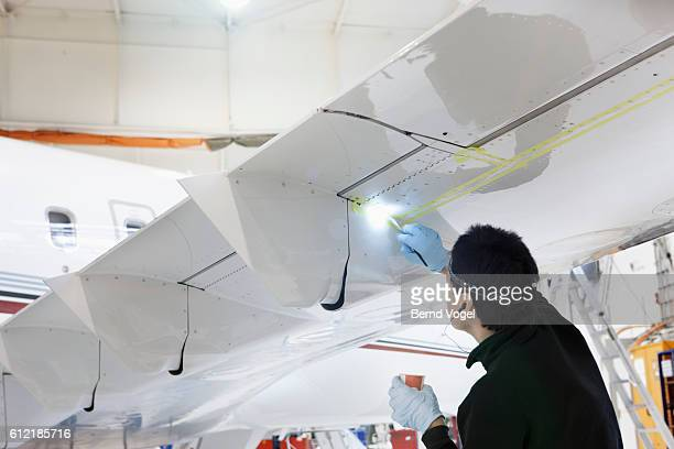 Aircraft factory worker painting underside of airplane wing
