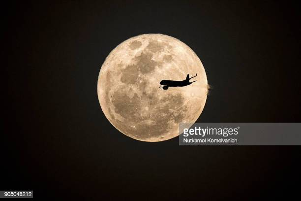 aircraft fly pass supermoon at night - supermoon stock pictures, royalty-free photos & images