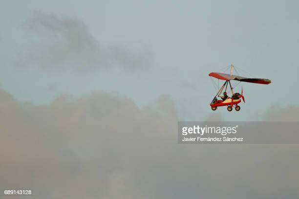a aircraft flying over the clouds. hand glider. - aereo ultraleggero foto e immagini stock