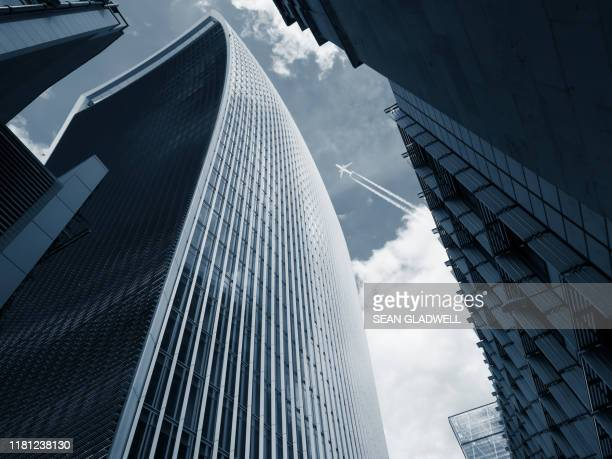 aircraft flying overhead between skyscrapers - aerospace stock pictures, royalty-free photos & images