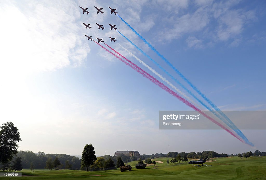 Aircraft from the British Royal Air Force's (RAF) Red Arrows aerobatic team create colored vapor trails as they fly over the Celtic Manor resort, the venue for the North Atlantic Treaty Organization (NATO) summit in Newport, U.K., on Friday, Sept. 5, 2014. U.K. Prime Minister David Cameron urged the leaders of France, Germany and Italy to be 'good to their word' and refrain from paying ransoms as a British hostage faces death at the hands of Islamist extremists. Photographer: Chris Ratcliffe/Bloomberg via Getty Images