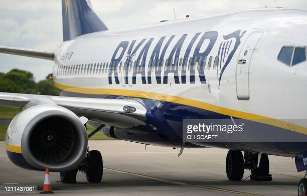 Aircraft grounded due to the COVID-19 pandemic, including planes operated by Ryanair, are pictured on the apron at Manchester Airport in Manchester,...