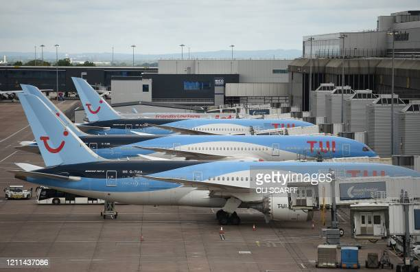 Aircraft grounded due to the COVID-19 pandemic, including planes operated by TUI, are pictured on the apron at Manchester Airport in Manchester,...
