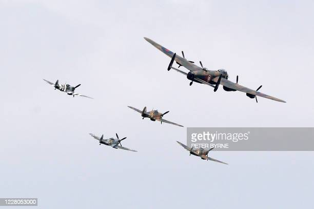 Aircraft including three Spitfires, a Hurricane and a Lancaster bomber, perform a fly-past during a national service of remembrance at the National...