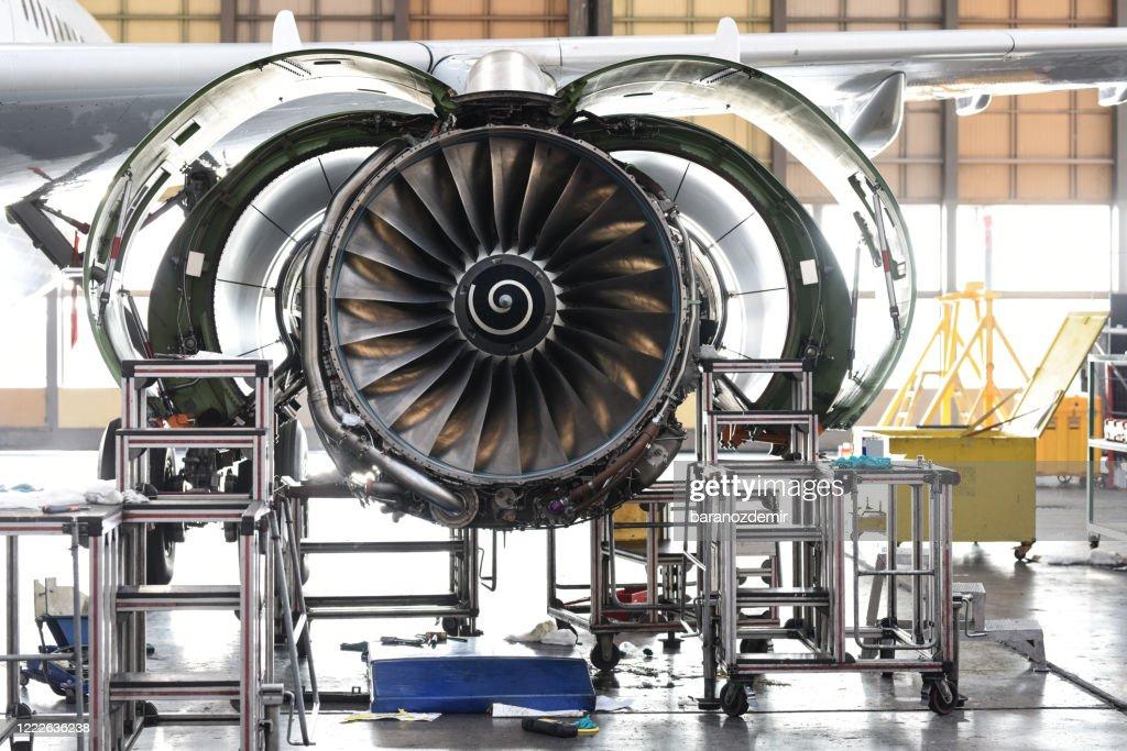 航空機の格納庫でのジェットエンジンのメンテナンス : ストックフォト