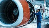 Aircraft maintenance mechanic with a flash light inspects plane engine in a hangar.