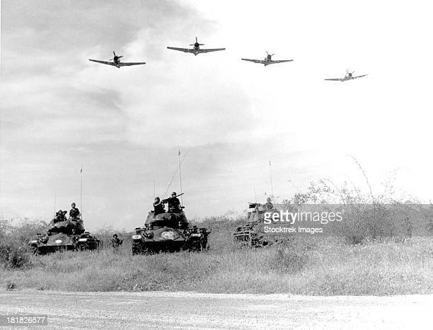 a-1h aircraft make a low level pass over vietnamese tanks and ground troops. - guerra de vietnam fotografías e imágenes de stock
