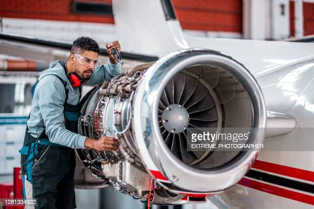aircraft mechanic checking jet engine of the airplane - air vehicle stock pictures, royalty-free photos & images