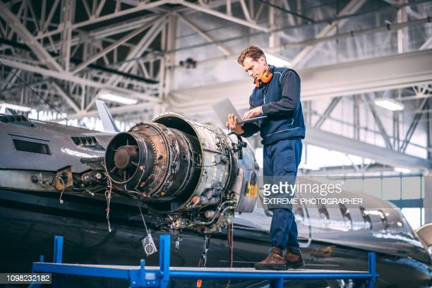 aircraft mechanic holding a laptop and diagnosing a jet engine of a small airplane while standing on a raised platform in a hangar - liquid crystal display stock pictures, royalty-free photos & images