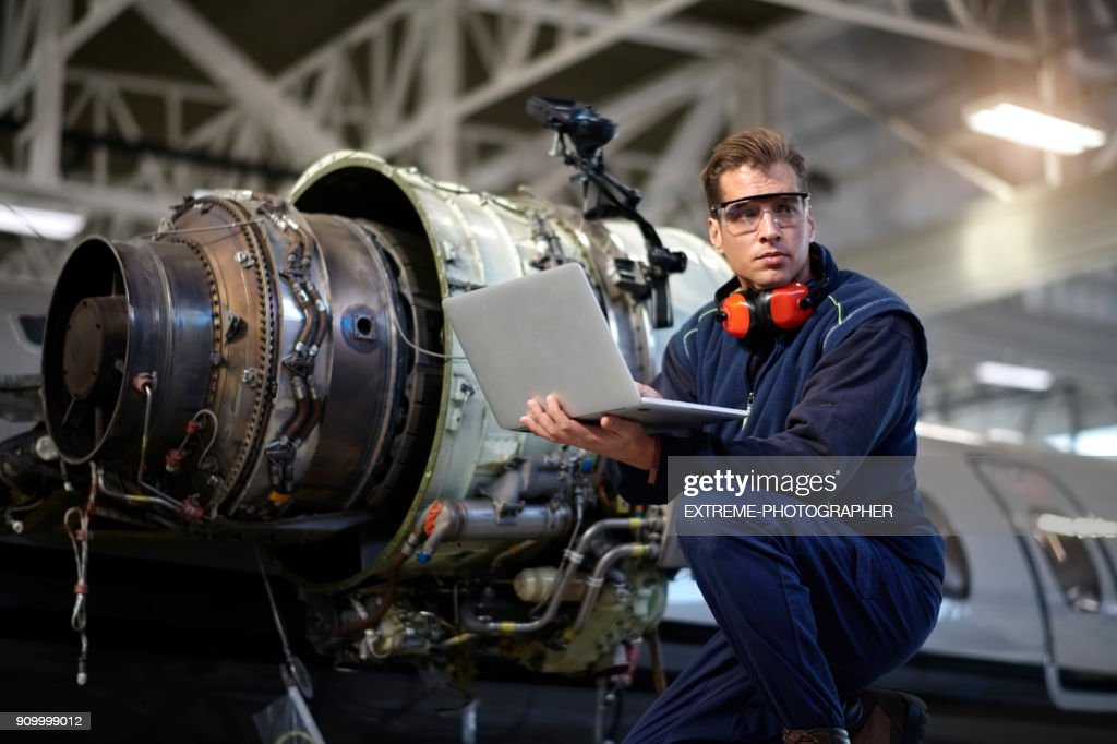 Aircraft mechanic in the hangar : Stock Photo