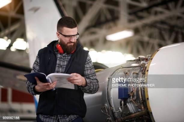 aircraft mechanic in the hangar - handbook stock photos and pictures