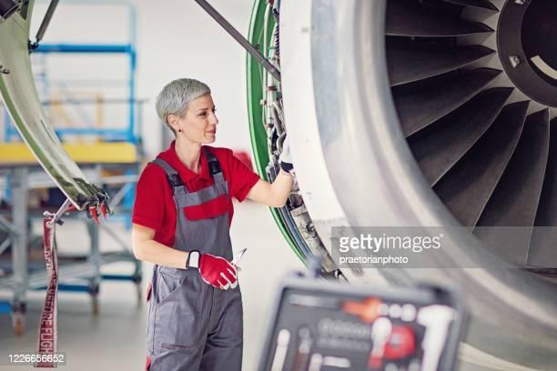 flugzeugmechaniker arbeitet in einem flugzeughangar - bildkomposition und technik stock-fotos und bilder