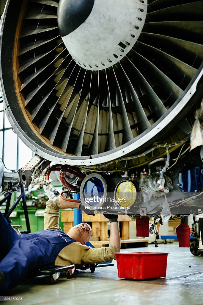 Aircraft Mechanic Lying Underneath A Jet Engine Stock Photo | Getty ...