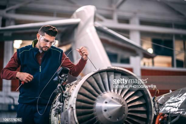 fluggerätmechaniker sondieren eine geöffnete triebwerk des flugzeugs mit einer tragbaren kamera und blick auf den monitor in der wartungshalle - flugzeugheck stock-fotos und bilder