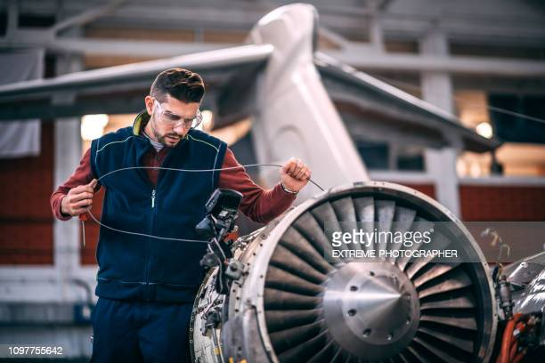 aircraft mechanic probing an opened jet engine of an airplane with a portable camera and looking at the monitor in the maintenance hangar - fuselage stock pictures, royalty-free photos & images