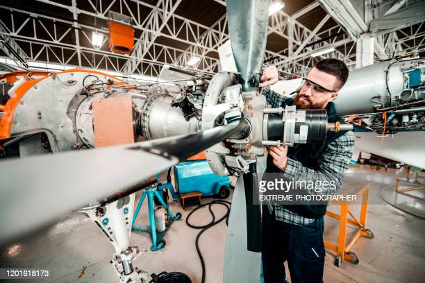 aircraft mechanic working on a propeller assembly of a small aircraft in a hangar - fuselage stock pictures, royalty-free photos & images