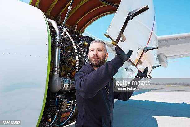 Aircraft mechnic in front of aircraft engine
