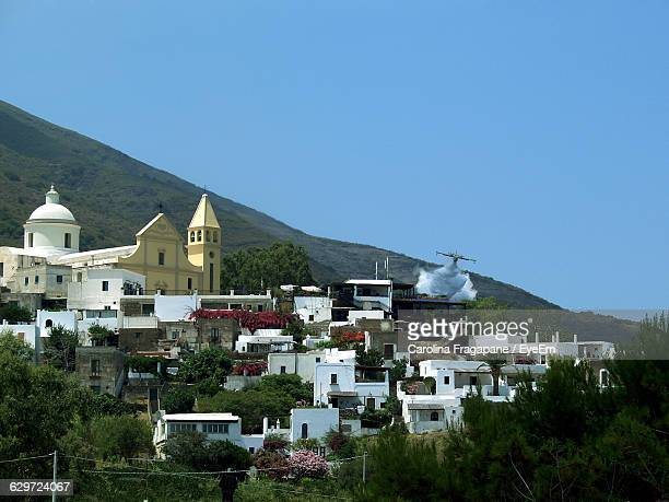 aircraft over houses against clear sky at aeolian islands - carolina fragapane stock pictures, royalty-free photos & images