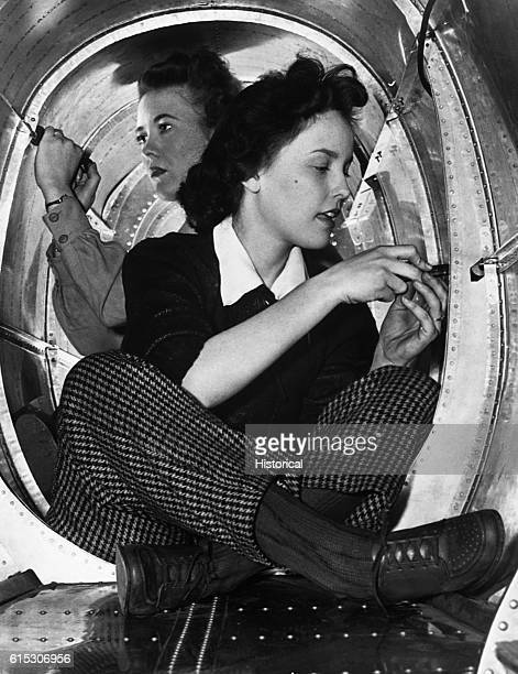 Aircraft production aides Ruby Reed and Merle Judd of the Grumman Aircraft Engineering Corporation work on the interior of a new plane