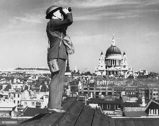 Aircraft spotter stands on the roof of a building in London St Paul's Cathedral stands in the background 1940
