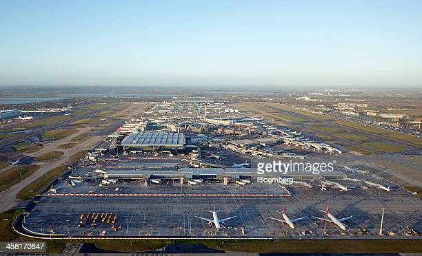 Aircraft stand parked at departure and arrival gates between the two runways at London Heathrow Airport in this aerial photograph looking west over...