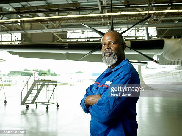 Aircraft technician by aero plane in hangar, portrait