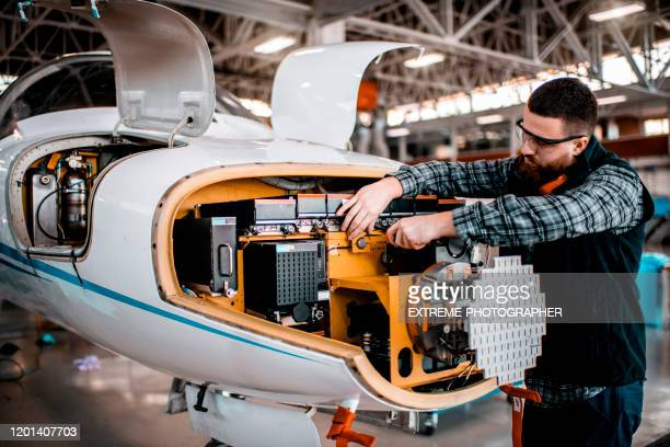 aircraft technician performing service on a radar array of an airplane in a maintenance hangar - fuselage stock pictures, royalty-free photos & images