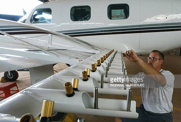 Aircraft technician Steve Bauer of US company Weather Modification Inc inspects wing mounted burnin silver iodide flare racks on a Piper Cheyenne II...