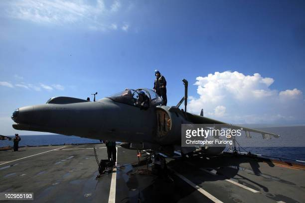 Aircraft technicians work on Harrier jets on the flight deck of HMS Ark Royal during Exercise Auriga on July 14 2010 at sea in Onslow Bay near North...