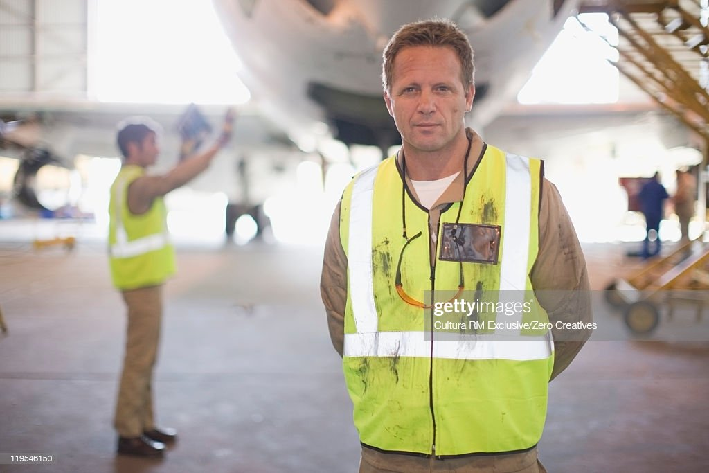Aircraft worker standing on airfield : Stock Photo