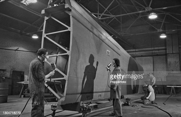 Aircraft workers use spray guns to paint camouflage finish on to the outer section of the main wing of an Avro Lancaster heavy bomber under...