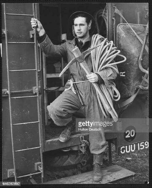 Aircraftman A. Ainsworth of the Royal Air Force leaves the store van with a rope, pick and axe ready for a rescue operation at Tayneuth Castle. He is...